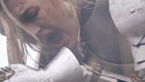 Die Blondine in der ritterlichen Rüstung verbiegt über die Klinge und schreit vom Leid stock video footage