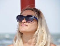 Die Blondine in der Sonnenbrille auf dem Strand Mädchen, das auf dem Strand stillsteht Lizenzfreie Stockfotografie