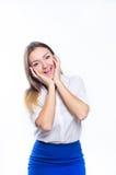 Die Blondine in der weißen Bluse hält Handlächelndes Gesicht Lizenzfreie Stockfotografie
