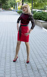 Die Blondine in einem roten Kleid auf der Stadtstraße Lizenzfreies Stockbild