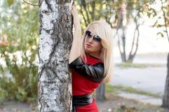 Die Blondine in einem roten Kleid an einem Baum im Fall Lizenzfreies Stockbild