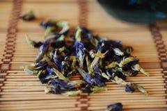 Die Blumen des thailändischen blauen Tees Anchan werden auf eine Bambusmattennahaufnahme zerstreut Stockbild
