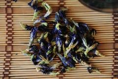 Die Blumen des thailändischen blauen Tees Anchan werden auf eine Bambusmattennahaufnahme zerstreut Stockfotos