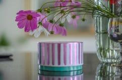 Die Blumen vom Vase lehnten sich über dem Kasten mit einem Geschenk stockbild