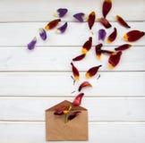 Die Blumenblätter von Blumen werden aus dem Umschlag auf Holztisch gegossen Stockbild