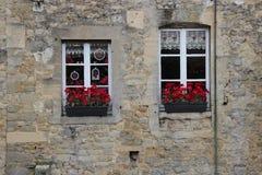 Die Blumenkästen, die mit roten Blumen gefüllt werden, verzieren die Fassade eines Hauses (Frankreich) Stockbilder