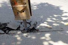Die Bohrmaschine der Straße graben Straßendecke stockbild