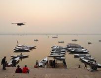 Die Boote von Varanasi mit fliegenden Unkosten des Vogels lizenzfreie stockbilder