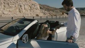 Die Bräutigamhilfe die Braut, zum vom Auto herauszunehmen stock footage