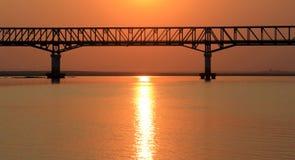 Die Brücke bei Sonnenuntergang auf dem Irrawaddy-Fluss lizenzfreie stockfotos