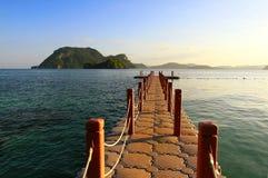 Die Brücke schwimmt und dehnt zum schönen Meer mit Berg, blauem Himmel, Wolke und Sonnenunterganglicht aus Stockbild