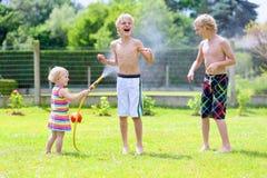 Die Brüder und Schwester, die mit Wasser spielen, bespritzen im Garten mit einem Schlauch Lizenzfreies Stockfoto