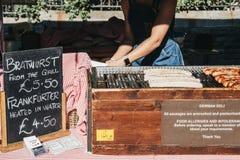 Die Bratwürste, die am deutschen Feinkostgeschäftmarkt grillen, klemmen am Stadt-Markt, London, Großbritannien fest stockbilder