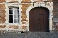 Die braune alte Tür und die Backsteinmauer Stockfotos