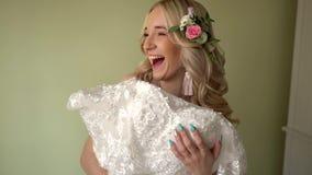 Die Braut bedeckt sich mit einem Kleid und lacht stock footage