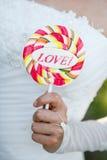 Die Braut, die eine Süßigkeit hält Stockfotografie