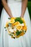 Die Braut, die einen Blumenstrauß mit gelben Blumen hält Lizenzfreies Stockfoto
