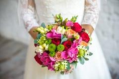 Die Braut, die Hochzeitsblumenstrauß des rosafarbenen Rosas von Rosen und von Liebe hält, blüht Stockfoto