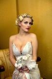 Die Braut, die mit einem Blumenstrauß blond ist, sitzt auf einem Stuhl Stockfoto
