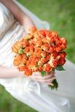 Die Braut, die orange Hochzeitsblumenstrauß anhält Stockbild