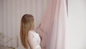 Die Braut in einem peignoir schaut und berührt ein Heiratskleid stock video footage