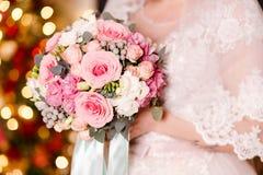 Die Braut in einem Schleier hält einen schönen Blumenstrauß von empfindlichen Rosen Die Lichter im Hintergrund lizenzfreies stockbild