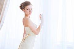 Die Braut in einem weißen Kleid über Vorhänge. Lizenzfreie Stockbilder