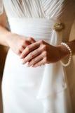 Die Braut in einem weißen Kleid, in einer Hand und in Fingern Stockfoto