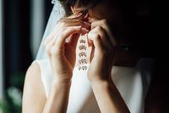 Die Braut in einem weißen Kleid trägt Goldohrringe mit Perlen stockbild