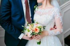 Die Braut in einem weißen Kleid und der Bräutigam in einem blauen Anzug stehen im Raum und halten einen Hochzeitsblumenstrauß Stockbilder