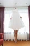 Die Braut hält ein Hochzeitskleid Lizenzfreies Stockbild