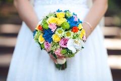 Die Braut hält einen farbigen Blumenstrauß in ihren Händen, Nahaufnahme Hände der Braut und des Bräutigams Lizenzfreie Stockfotografie