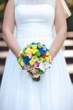 Die Braut hält einen farbigen Blumenstrauß in ihren Händen, Nahaufnahme Hände der Braut und des Bräutigams Stockfotografie