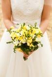 Die Braut hält einen Hochzeitsblumenstrauß an Lizenzfreie Stockfotografie