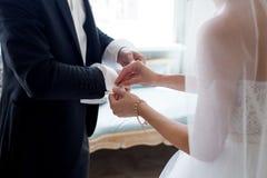 Die Braut hilft ihrem Verlobten, Manschettenknöpfe zu befestigen Heiratssorgen Stockfotografie