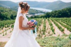 Die Braut im Profil auf einem Hintergrund des schönen Grüns und des Himmels bewundert ihren Hochzeitsblumenstrauß lizenzfreies stockfoto