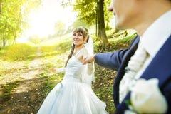 Die Braut ist führender Bräutigam auf einer Straße Stockbild