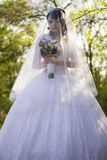 Die Braut ist geschlossener Schleier mit einem Blumenstrauß in der Hand Lizenzfreie Stockbilder