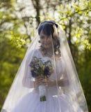 Die Braut ist geschlossener Schleier mit einem Blumenstrauß in der Hand Stockfotos