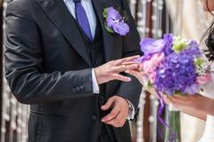 Die Braut kleidet einen Ehering zum Bräutigam Lizenzfreie Stockfotos