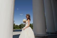 Die Braut mit einem Blumenstrauß an den Spalten. Lizenzfreie Stockfotos
