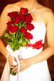 Die Braut mit einem Blumenstrauß der roten Farben Stockfoto