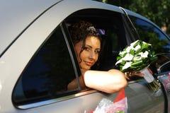 Die Braut mit einem Blumenstrauß im Auto stockfoto