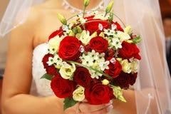 Die Braut mit einem Hochzeitsblumenstrauß. Stockfotografie