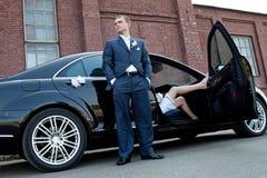 Die Braut mit einer Blume Bräutigam nahe bei einem Exekutivauto, das Braut sitzt lizenzfreie stockfotografie