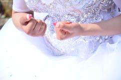 Die Braut ` s Hand in einem weißen Kleid mit einer Maniküre und einem Goldring Stockfoto