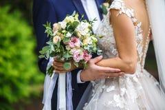 Die Braut setzte ihre Hände auf die Schultern des Bräutigams Braut mit einem Blumenstrauß von Umarmungen der Rosa- und weißerrose lizenzfreie stockfotos