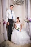 Die Braut sitzt in einem Stuhl und der Bräutigam steht nahe Braut im Raum stockfotografie