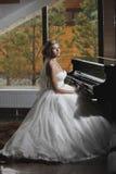 Die Braut sitzt am Klavier Lizenzfreie Stockfotos