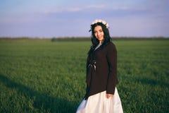 Die Braut steht auf einem Gebiet bei dem Sonnenuntergang und trägt eine gestrickte Strickjacke, ein kalter Abend lizenzfreie stockfotografie
